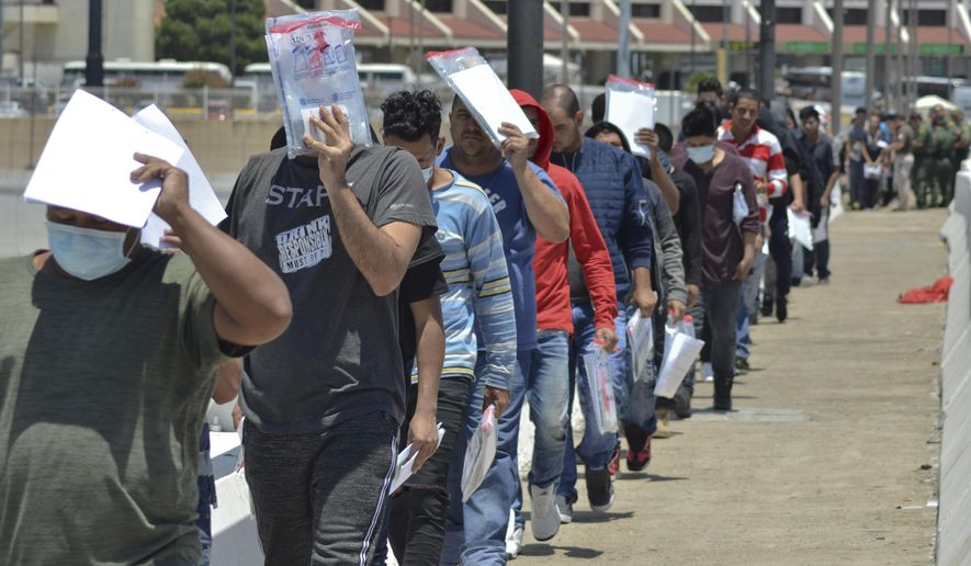 In this July 25, 2019, file photo, United States Border Patrol officers return a group of migrants back to the Mexico side of the border as Mexican immigration officials check the list, in Nuevo Laredo, Mexico. Nuevo Laredo continues to be a dangerous place for asylum seekers waiting to cross into the United States after being sent back to await the outcome of their petitions, according to a report released Tuesday, Feb. 11, 2020. (AP Photo/Salvador Gonzalez, File)