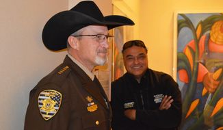 Lea County Sheriff Corey Helton, left, waits with McKinley County Sheriff Ronald Silversmith, right, outside the New Mexico House chamber before a debate on a proposed red-flag gun bill in Santa Fe, N.M., Tuesday, Feb. 11, 2020. Democratic legislators in New Mexico are pushing forward with a red-flag gun proposal at a legislative committee meeting that offers a final opportunity for public comment. (AP Photo/Russell Contreras)