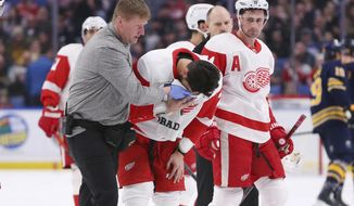 Detroit Red Wings forward Brendan Perlini (29) is helped off the ice by trainer and forward Dylan Larkin (71) during the first period of an NHL hockey game against the Buffalo Sabres, Tuesday, Feb. 11, 2020, in Buffalo, N.Y. (AP Photo/Jeffrey T. Barnes)