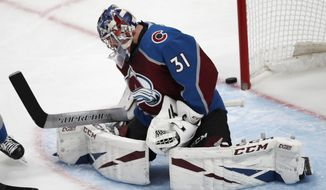 Colorado Avalanche goaltender Philipp Grubauer misses the puck as it flies past the net in the first period of an NHL hockey game against the Ottawa Senators Tuesday, Feb. 11, 2020, in Denver. (AP Photo/David Zalubowski)