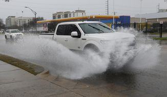 A vehicle sprays water as rain falls in downtown Jackson, Miss., Tuesday, Feb. 11, 2020, making for cascades of splashed water as traffic drives through. The National Weather Service says minor to moderate flooding is expected from central Mississippi to north Georgia following downpours. (AP Photo/Rogelio V. Solis)