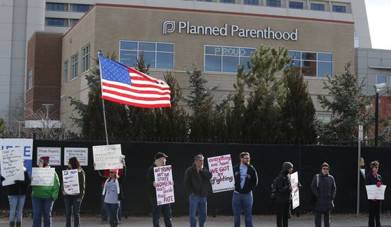 In this Feb. 11, 2017, file photo, pro-choice counterprotesters hold signs supporting a woman's right to choose abortion, as nearby anti-abortion activists held a rally in front of Planned Parenthood of the Rocky Mountains, in Denver. (AP Photo/Brennan Linsley, File)