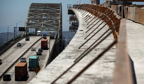 In this July 2, 2018, file photo, traffic moves on the old Gerald Desmond Bridge next to its replacement bridge under construction in Long Beach, Calif. President Donald Trump pronounced himself eager to work with Congress on a plan to rebuild America's crumbling roads and bridges, but offered no specifics during his State of the Union speech on what kind of deal he would back. (AP Photo/Jae C. Hong, File)