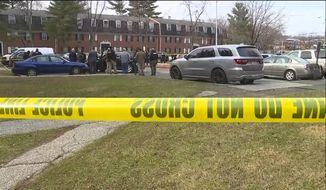 This image provided by WMAR-2 News shows emergency and law enforcement officials responding to the scene of a shooting, Wednesday, Feb. 12, 2020, in Baltimore. Two law enforcement officers with a fugitive task force were injured and a suspect died in a shooting on Wednesday, the U.S. Marshals Service said. (WMAR-2 News via AP)