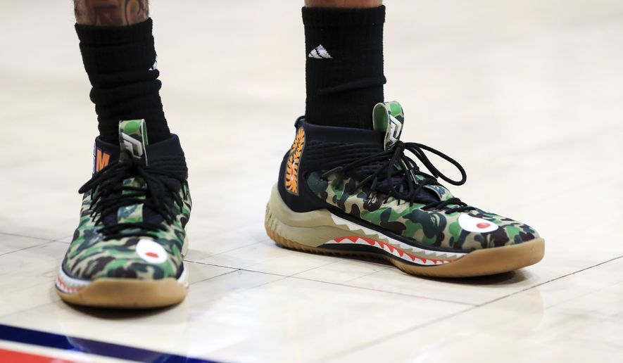 A view of the camouflage Adidas shoes worn by Rhode Island's Jeff Dowtin (11) in the first half in an NCAA college basketball game against Dayton, Tuesday, Feb. 11, 2020, in Dayton, Ohio. Dayton won 81-67. (AP Photo/Aaron Doster) ** FILE **