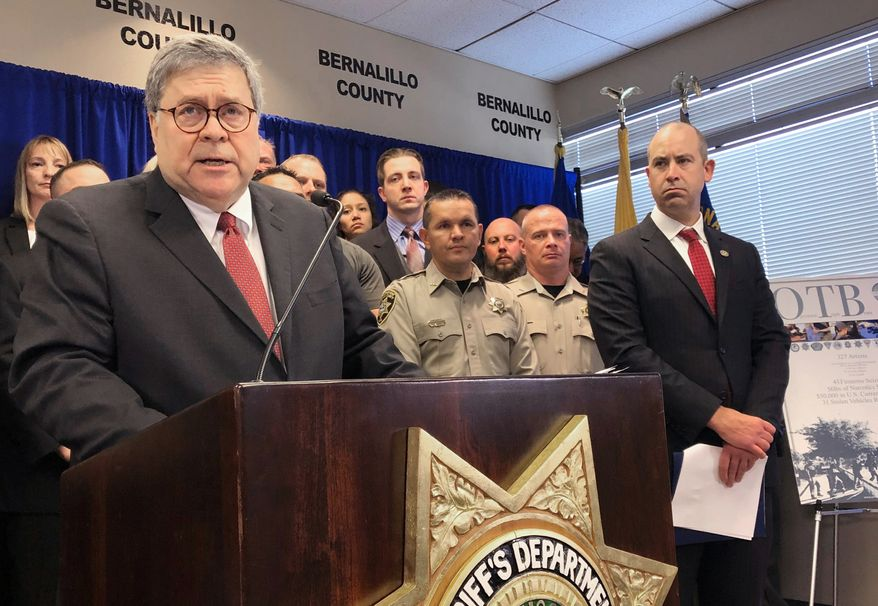 In this Nov. 12, 2019, photo, U.S. Attorney General William Barr, left, stands with other federal and officials at a news conference at the office of the Bernalillo County Sheriff in Albuquerque, N.M. New Mexico's most populous city stands to lose out on millions of dollars in crime-fighting grants due to its status as a sanctuary city, but some elected officials said Wednesday, Feb. 12, 2020, the U.S. Justice Department is holding out the promise of more federal funding to get Albuquerque to reconsider policies that prevent the sharing of information with federal immigration authorities. The Justice Department has reached out to the Albuquerque Police Department about funds available under Operation Relentless Pursuit, the initiative announced in December by Attorney General William Barr to combat violent crime in seven of America's most violent cities. (AP Photo/Mary Hudetz) **FILE**