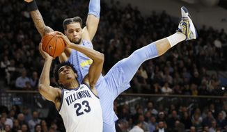 Villanova's Jermaine Samuels (23) tries to get a shot past Marquette's Theo John during the second half of an NCAA college basketball game Wednesday, Feb. 12, 2020, in Villanova, Pa. (AP Photo/Matt Slocum)