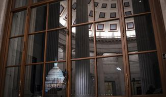 The Capitol is seen amid reflections of the Russell Senate Office Building in Washington. On Wednesday, Feb. 12, the Treasury Department releases federal budget data for January. (AP Photo/J. Scott Applewhite, File)