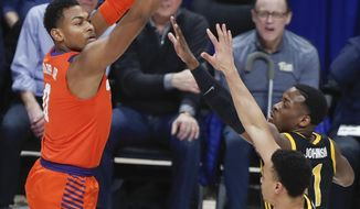 Clemson's Clyde Trapp shoots over Pittsburgh's Xavier Johnson (1) and Trey McGowens during the first half of an NCAA college basketball game Wednesday, Feb. 12, 2020, in Pittsburgh. (AP Photo/Keith Srakocic)