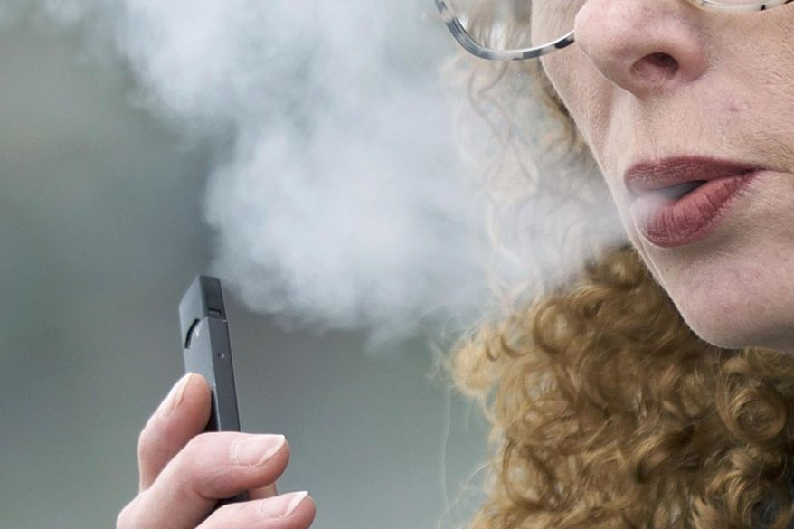 In this April 16, 2019, photo, a woman exhales while vaping from a Juul pen e-cigarette in Vancouver, Wash. (AP Photo/Craig Mitchelldyer) ** FILE **