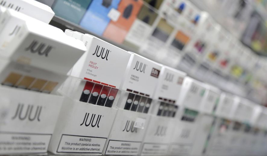 In this Dec. 20, 2018, photo, Juul products are displayed at a smoke shop in New York on Wednesday, Feb. 12, 2020. (AP Photo/Seth Wenig) **FILE**