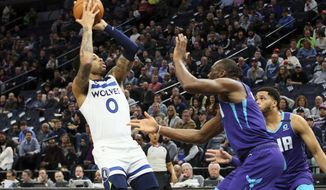 Charlotte Hornets' P.J. Washington Jr., right, pressures Minnesota Timberwolves' James Johnson into passing the ball during the first half of an NBA basketball game Wednesday, Feb. 12, 2020, in Minneapolis. (AP Photo/Jim Mone)
