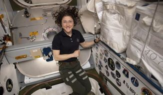In this June 2019 photo made available by NASA, astronaut Christina Koch poses for a portrait inside of the vestibule between a SpaceX Dragon cargo craft and the Harmony module of the International Space Station. Still fresh from space, NASA's new record-setting astronaut says that aside from sore muscles and feelings of off-balance, she's readjusting well to gravity after nearly 11 months in space. Koch met with reporters on Wednesday, Feb. 12, 2020, six days after returning from the International Space Station. Her 328-day mission was the longest ever by a woman. (NASA via AP)