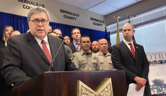 In this Nov. 12, 2019, file photo, U.S. Attorney General William Barr, left, stands with other federal and officials at a news conference at the office of the Bernalillo County Sheriff in Albuquerque, N.M. (AP Photo/Mary Hudetz, File)