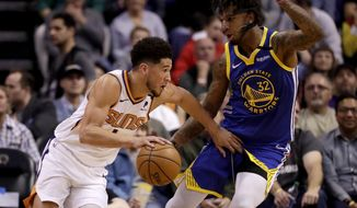 Phoenix Suns guard Devin Booker (1) drives around Golden State Warriors forward Marquese Chriss (32) during the first half of an NBA basketball game, Wednesday, Feb. 12, 2020, in Phoenix. (AP Photo/Matt York)