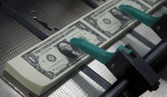 FILE- In this Nov. 15, 2017, file photo, new $1 bills with the signatures of U.S. Treasurer Jovita Carranza and Treasury Secretary Steven Mnuchin are cut and stacked at the Bureau of Engraving and Printing in Washington. Fidelity Investments says the average 401(k) balance rose to a record $112,300 last year. Part of the gain was due to surging markets, as stocks and bonds of all types rallied.  (AP Photo/Jacquelyn Martin, File)