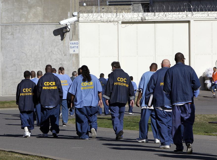 FILE - In this Feb. 26, 2013, file photo, inmates walk through the exercise yard at California State Prison Sacramento, near Folsom, Calif. California arrest rates have dropped nearly 60 percent since 1989, yet blacks are three times more likely to be arrested than whites, according to a report released by the Public Institute of California, Monday Dec. 3, 2018. (AP Photo/Rich Pedroncelli, File)
