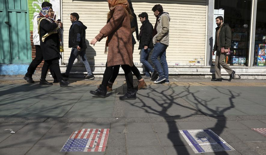 Pedestrians walk past representations of the U.S. and Israeli flags pasted on the ground on Enqelab-e-Eslami (Islamic Revolution) street in downtown Tehran, Iran, Thursday, Feb. 13, 2020. Thousands of Iranian candidates approved to run in parliamentary elections kicked off their campaigns Thursday ahead of next week's vote, even after authorities barred thousands of others from running, mainly reformists and moderates. (AP Photo/Vahid Salemi)