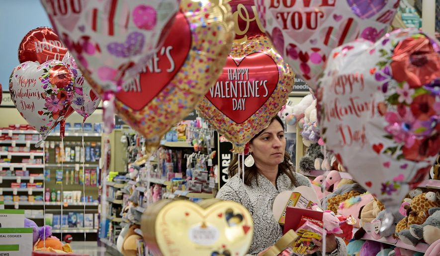 Jessica DeMedeiros is surrounded by Valentine's Day themed balloons, as she picks out some gifts for her loved ones in New Bedford, Mass., on  Thursday, Feb. 13, 2020. (Peter Pereira/Standard Times via AP)