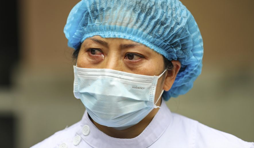 A nurse tears up as she talks about the situation in Jinyintan Hospital, designated for critical COVID-19 patients, in Wuhan in central China's Hubei province Thursday, Feb. 13, 2020. China on Thursday reported 254 new deaths and a spike in virus cases of 15,152, after the hardest-hit province of Hubei applied a new classification system that broadens the scope of diagnoses for the outbreak, which has spread to more than 20 countries. (Chinatopix Via AP)