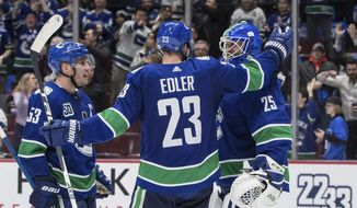 Vancouver Canucks' Bo Horvat, Alexander Edler and goalie Jacob Markstrom celebrate after Vancouver defeated the Chicago Blackhawks 3-0 during an NHL hockey game Wednesday, Feb. 12, 2020, in Vancouver, British Columbia. (Darryl Dyck/The Canadian Press via AP)