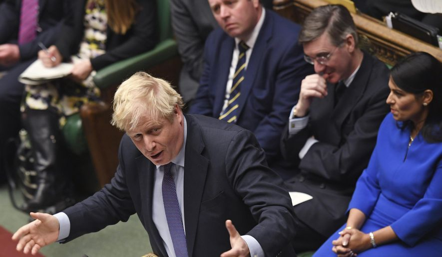 In this photo made available from the U.K. Parliament, Britain's Prime Minister Boris Johnson reacts as he gives an answer during the weekly Prime Minister's Questions session in the House of Commons in London, Wednesday, Feb. 12, 2020. Behind from right, Priti Patel, Jacob Rees-Mogg, Mark Spencer. (Jessica Taylor/House of Commons via AP)