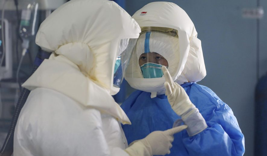 Medical staff work in the negative-pressure isolation ward in Jinyintan Hospital, designated for critical COVID-19 patients, in Wuhan in central China's Hubei province Thursday, Feb. 13, 2020. China on Thursday reported 254 new deaths and a spike in virus cases of 15,152, after the hardest-hit province of Hubei applied a new classification system that broadens the scope of diagnoses for the outbreak, which has spread to more than 20 countries. (Chinatopix Via AP)