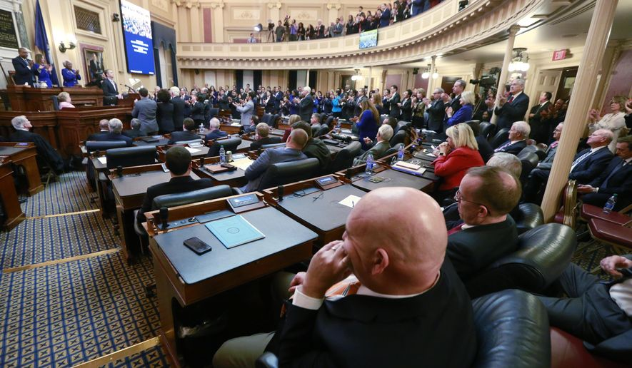 FILE - In this Jan. 8, 2020 file photo, House Republicans sit in their seats as Democratic lawmakers applaud Virginia Gov. Ralph Northam as he delivers his State of the Commonwealth address before a joint session of the Assembly at the state Capitol in Richmond, Va. Some criminal justice activists are disappointed by the number of reform proposals that have stalled in Virginia's legislature this year, despite a new Democratic majority. (AP Photo/Steve Helber, File)