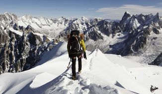 """FILE - In this file photo taken on Oct. 12, 2011, an alpinist heads down a ridge on the Aiguille du Midi (3,842 meters; 12 605 feet), towards the Vallee Blanche on the Mont Blanc massif, in the Alps, near Chamonix. French President Emmanuel Macron declared the battle against climate change and environmental destruction to be """"the fight of the century"""" Thursday Feb. 13, 2020 after visiting a melting glacier in the Alps. (AP Photo/David Azia,File)"""