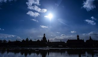 The sun shines behind Dresden's Old Town skyline with the Frauenkirche cathedral (Church of Our Lady), reflected in a puddle, in Dresden, Germany, Tuesday, Feb. 11, 2020 two days before the 75th anniversary of the Allied bombing of Dresden during WWII. British and U.S. bombers on Feb. 13-14, 1945 destroyed Dresden's centuries-old baroque city center. (AP Photo/Jens Meyer)