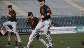 San Francisco Giants catcher Buster Posey, right, jumps in the air as he warms up with teammates during spring training baseball workouts for pitchers and catchers Wednesday, Feb. 12, 2020, in Scottsdale, Ariz. (AP Photo/Ross D. Franklin)