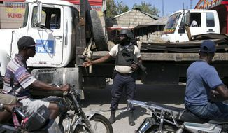 In this Feb. 12, 2020 photo, a police officer directs motorcycles to speed up during a protest against the dire security situation in Port-au-Prince, Haiti. Two years after the departure of UN peacekeepers, some police are protesting working conditions and demanding a union, which the government says would be illegal. (AP Photo/Dieu Nalio Chery)