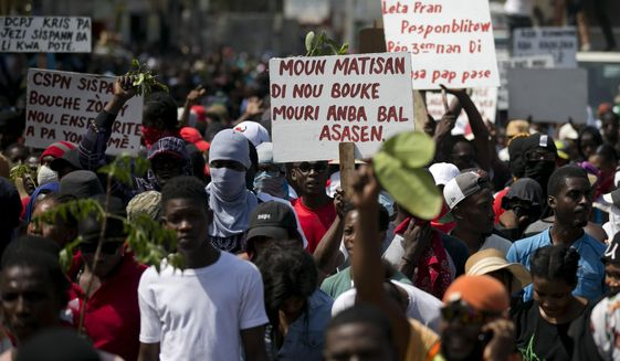 "In this Feb. 12, 2020 photo, a protester holds a sign that reads in Creole ""The people of Martissant are tired of dying from criminals' bullets,"" referring to one of the capital's most dangerous neighborhoods, during a march against violence in Port-au-Prince, Haiti. Two years after the departure of U.N. peacekeepers, young bandits with automatic weapons randomly halt cars on the main routes in and out of the capital. (AP Photo/Dieu Nalio Chery)"