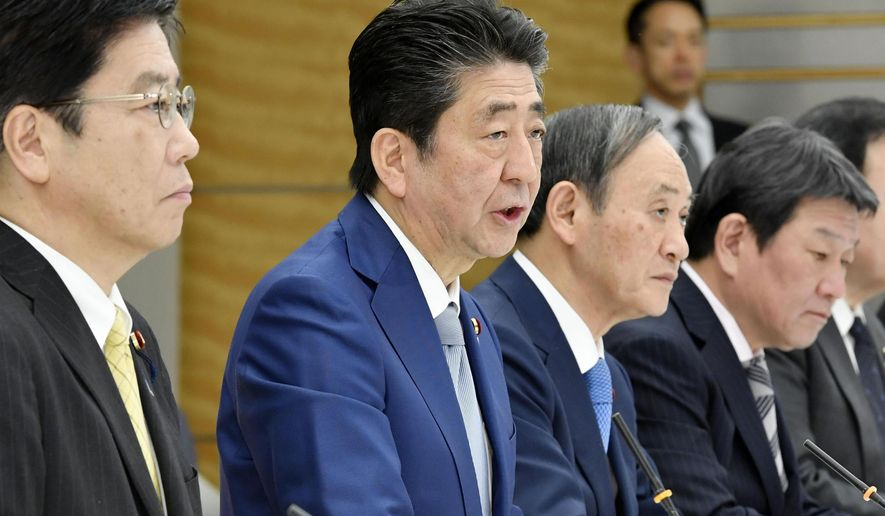 Japan's Prime Minister Shinzo Abe, second left, speaks at a meeting against a new coronavirus, at his official residence in Tokyo Thursday, Feb. 13, 2020. Abe on Thursday announced a series of measures totaling 15.3 billion yen to deal with the spread of coronavirus. (Yoshitaka Sugawara/Kyodo News via AP)