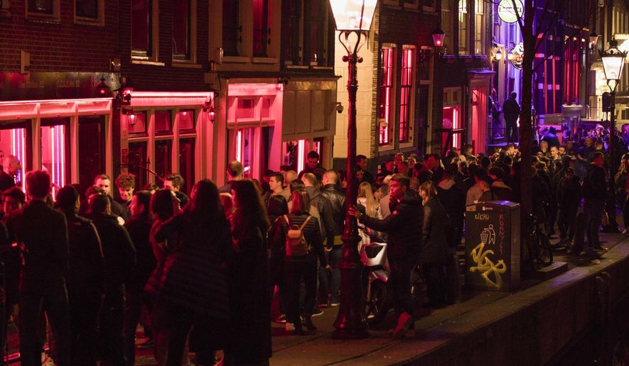 """-FILE- In this Friday March 29, 2019, file image tourists bathing in a red glow emanating from the windows and peep shows' neon lights are packed shoulder to shoulder as they shuffle through the alleys in Amsterdam's red light district, Netherlands. The capital is banning tours that take groups past the city's famed """"windows,"""" where sex workers pose in the Red Light District, the latest attempt to rein in the nuisance of over-tourism. (AP Photo/Peter Dejong, File)"""