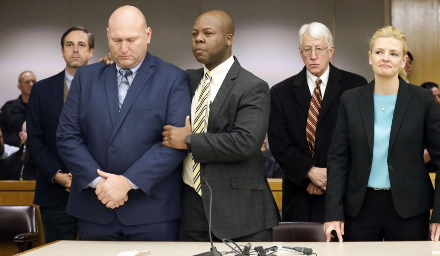 Attorney Keith Harris (center) congratulates former Dallas police officer Christopher Hess (left) as he was found not guilty by a jury in the 292nd District Court at the Frank Crowley Courts Building in Dallas, Thursday, Feb. 13, 2020. Hess was absolved of aggravated assault in the fatal shooting of 21-year-old Genevive Dawes. (Tom Fox/The Dallas Morning News via AP)