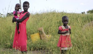 """In this photo taken Monday, Oct. 1, 2018, children stand in a field by the side of the road between Melut and in Paloch town, in South Sudan. The oil industry in South Sudan has left a landscape pocked with hundreds of open waste pits with the water and soil contaminated with toxic chemicals and heavy metals, and accounts of """"alarming"""" birth defects, miscarriages and other health problems, according to four environmental reports obtained by The Associated Press. (AP Photo/Sam Mednick)"""