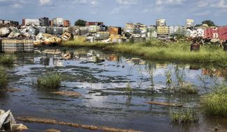 """In this photo taken Monday, Oct. 1, 2018, containers used for hazardous chemicals lie exposed and piled up at a junkyard run by the Chinese-led Dar Petroleum Operating Company in Gumry, near Paloch, in South Sudan. The oil industry in South Sudan has left a landscape pocked with hundreds of open waste pits with the water and soil contaminated with toxic chemicals and heavy metals, and accounts of """"alarming"""" birth defects, miscarriages and other health problems, according to four environmental reports obtained by The Associated Press. (AP Photo/Sam Mednick)"""