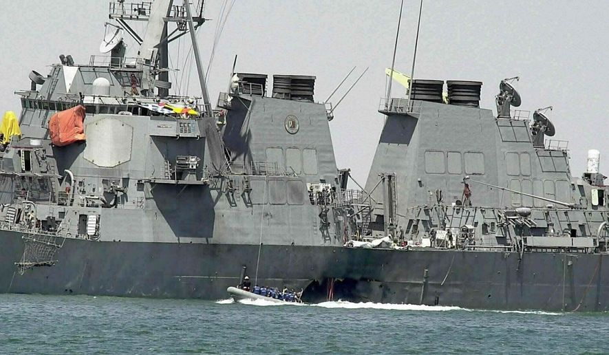 In this Oct. 15, 2000, file photo, experts in a speed boat examine the damaged hull of the USS Cole at the Yemeni port of Aden after an al Qaeda attack that killed 17 sailors. (AP Photo/Dimitri Messinis, File)