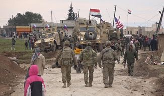 In this frame grab from video, Russian, Syrian and others gather next to an American military convoy stuck in the village of Khirbet Ammu, east of Qamishli city, Syria, Wednesday, Feb. 12, 2020.  (AP Photo)  **FILE**