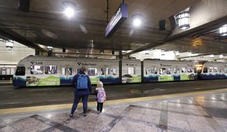 FILE - In this Nov. 6, 2019, file photo, southbound passengers wait as they look across at a northbound Sound Transit light rail train at an underground station in downtown Seattle. The Washington Supreme Court on Thursday, Feb. 13, 2020, upheld vehicle registration tax increases in the Puget Sound area, a decision that preserves billions of dollars in voter-approved money earmarked for light trail and other projects. (AP Photo/Elaine Thompson, File)