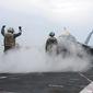 A Sailor directs an F/A-18F at sea in this U.S. Navy photo.