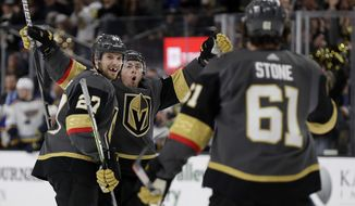 Vegas Golden Knights center Jonathan Marchessault, rear, celebrates after scoring against the St. Louis Blues with defenseman Shea Theodore (27) and right wing Mark Stone (61) during the second period of an NHL hockey game Thursday, Feb. 13, 2020, in Las Vegas. (AP Photo/Isaac Brekken)