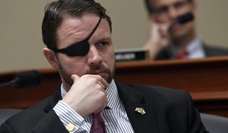 In this Tuesday, March 12, 2019, file photo, U.S. Rep. Dan Crenshaw, R-Texas, left, listens as Office of Management and Budget Acting Director Russell Vought testifies before the House Budget Committee on Capitol Hill in Washington, during a hearing on the fiscal year 2020 budget. (AP Photo/Susan Walsh, File)