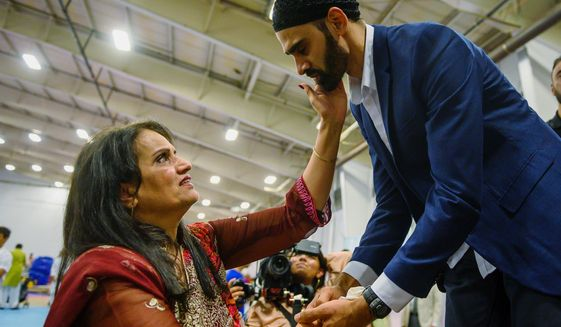 """FILE - In this Aug. 11, 2019, file photo, Hamid Hayat, right, is welcomed by the community after making his first public appearance at a news conference that coincided with Eid al-Adha, also called the """"Festival of the Sacrifice,"""" an Islamic holiday, in Sacramento, Calif. Federal prosecutors in California on Friday, Feb. 14, 2020, ended what once was among the nation's highest profile anti-terrorism cases, after a judge earlier overturned Hayat's conviction that grew from conspiracy allegations in the wake of the 2001 terrorist attacks. (Daniel Kim/The Sacramento Bee via AP, File)"""