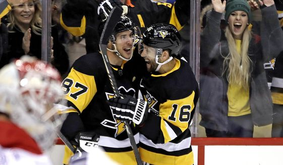 Pittsburgh Penguins' Jason Zucker (16) celebrates his goal with Sidney Crosby (87) during the second period of the team's NHL hockey game against the Montreal Penguins in Pittsburgh, Friday, Feb. 14, 2020. (AP Photo/Gene J. Puskar)