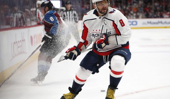 Washington Capitals left wing Alex Ovechkin, front, fights for control of the puck with Colorado Avalanche defenseman Cale Makar in the first period of an NHL hockey game Thursday, Feb. 13, 2020, in Denver. (AP Photo/David Zalubowski) ** FILE **