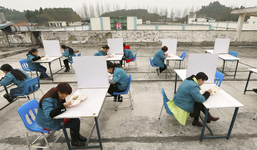 In this Friday, Feb. 14, 2020, photo, factory workers are separated by partitions as a precaution against infection as they take their lunch break on the roof of an electronics factory in Suining in southwestern China's Sichuan Province. China reported Saturday a figure of 2,641 new virus cases, a major drop from the higher numbers in recent days since a broader diagnostic method was implemented. (Chinatopix via AP)
