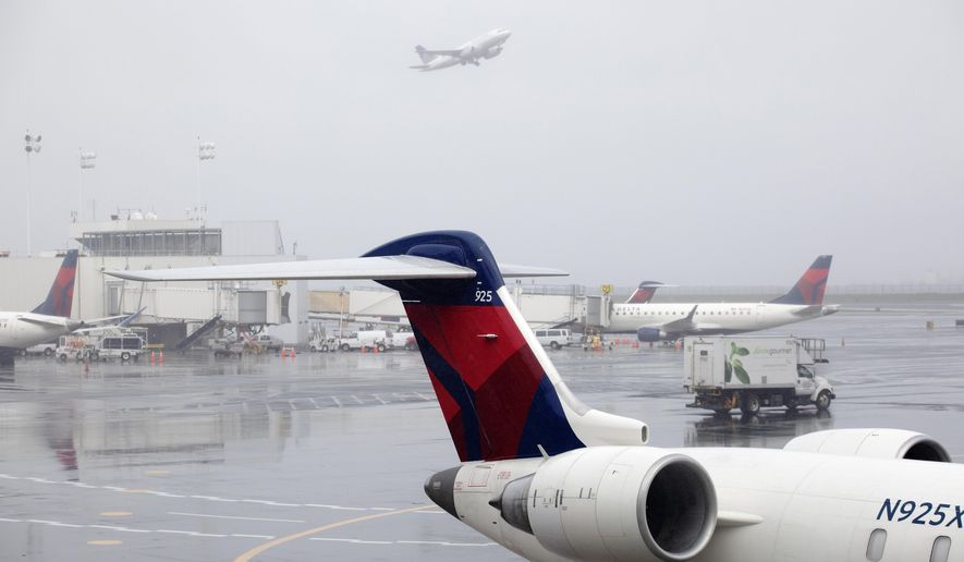 FILE - In this Oct. 29, 2019, file photo Delta planes are parked at the new $3.9 billion Terminal C at LaGuardia Airport in New York. Delta Air Lines said Friday, Feb. 14, 2020, that it will invest $1 billion over the next 10 years in measures designed to offset climate-warming carbon emissions from its planes. (AP Photo/Mark Lennihan, File)