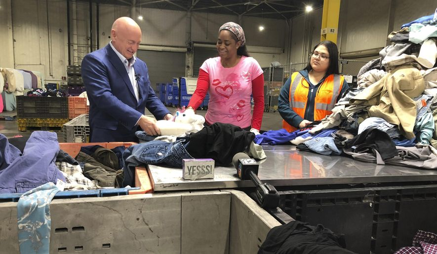 "Democratic U.S. Senate candidate Mark Kelly of Arizona speaks to workers sorting donated items at a Goodwill distribution center in Phoenix on Friday, Feb. 14, 2020. Kelly later told reporters The Trump administration's plan to divert money from defense projects to build a wall along the Mexican border could hurt Arizona's military industry to pay for a barrier that ""isn't necessary."" (AP Photo/Jonathan J. Cooper)"